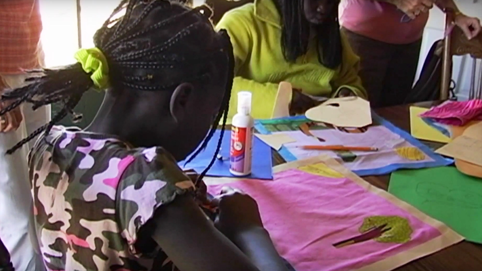 After cutting the pieces, the students glue them to the block fabric. From the documentary The Quilted Conscience