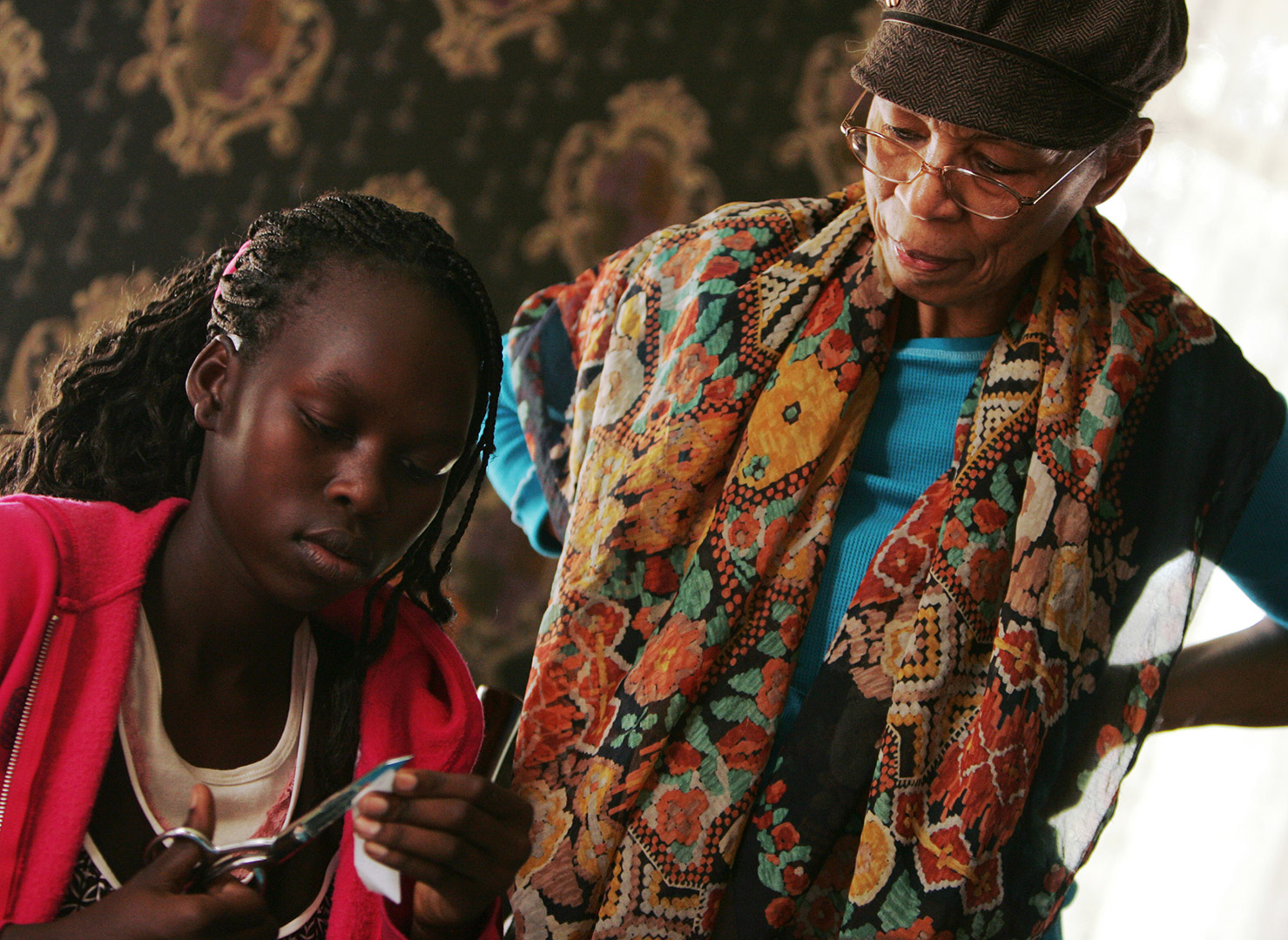Peggie Hartwell guides Wajdan Yusif as she cuts fabric. Photo by Scott Kingsley, Property of The Grand Island Independent http://theindependent.com
