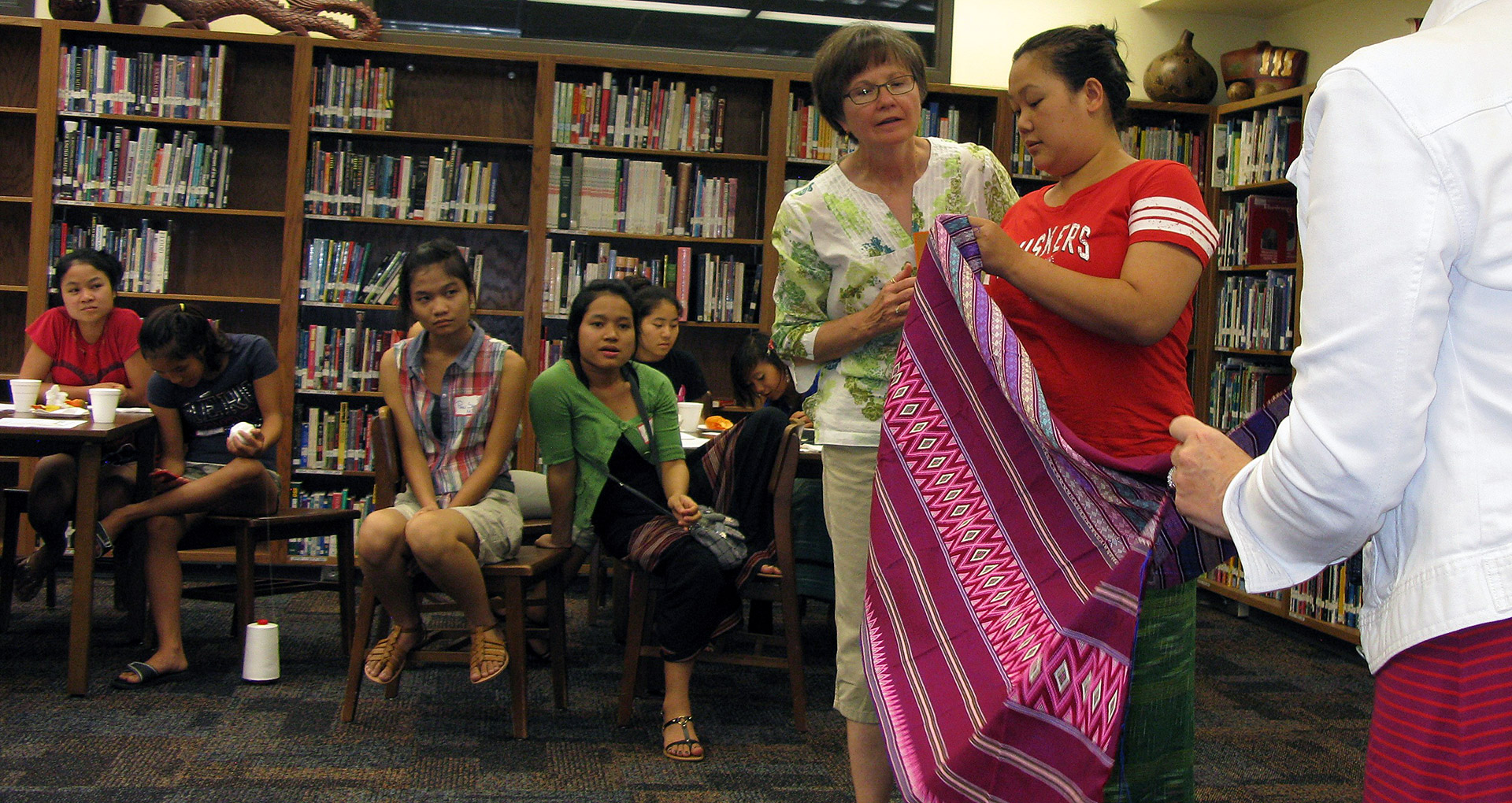Ruth Kupfer helps Karen mother show off traditional woven fabric. Courtesy Ruth Kupfer, Lincoln Quilt Coordinator