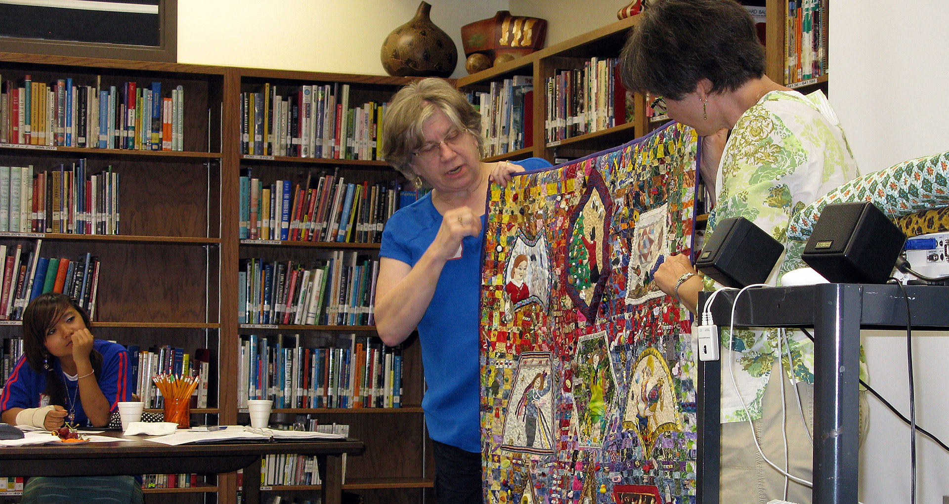 Sandra Anderson & Ruth Kupfer hold up a quilt example. Courtesy Ruth Kupfer, Lincoln Quilt Coordinator
