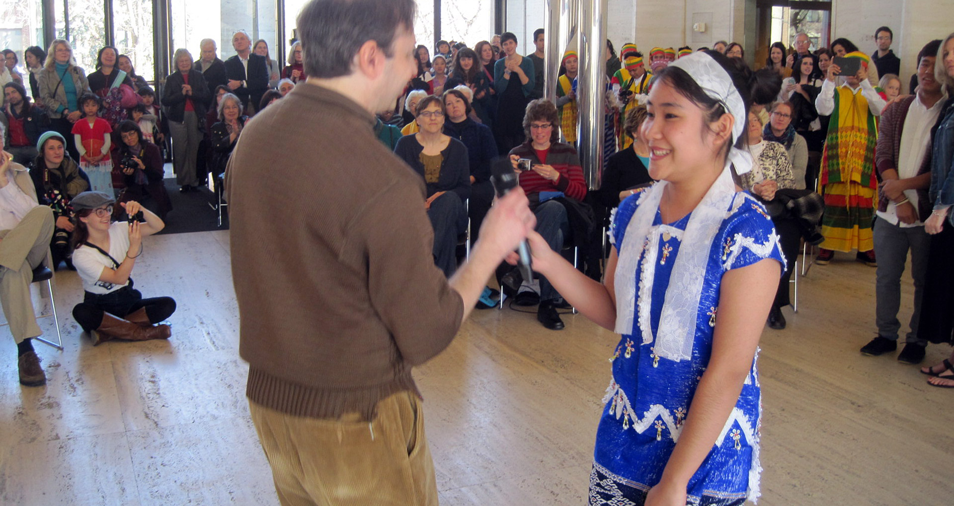 TQC Project Director John Sorensen hands the mic to Mu Wah, one of the student quilters. Courtesy Christine Lesiak
