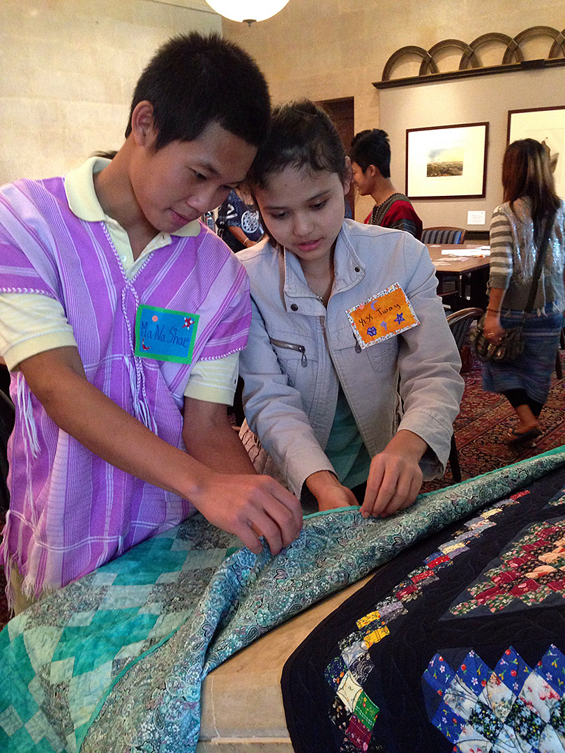 Examining the backing of a quilt. Courtesy Joslyn Art Museum